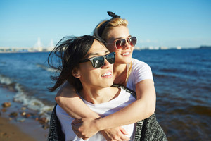 Loving young couple wearing sunglasses enjoying picturesque view while walking along seashore, blue water and cloudless sky on background