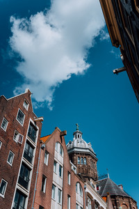 Low angle of narrow dutch houses with dome of St. Nicolas church in Amsterdam against blue sky and white cloud