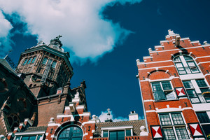 Low angle of traditional dutch house facade and St. Nicolas church in Amsterdam against blue sky and white cloud