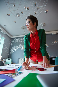 Low angle shot of successful businesswoman wearing colorful casual clothes and glasses standing at table in modern office working with creative project