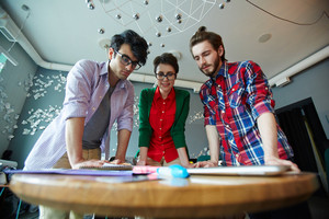 Low angle shot of team of young creative people wearing casual clothes collaborating at meeting in modern office standing round small table and looking at supplies laid out on it, brainstorming ideas