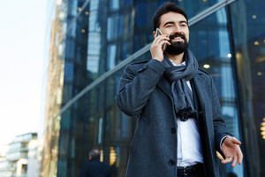 Low angle view of cheerful middle-aged businessman answering to phone call while standing at modern glass office building, waist-up portrait
