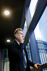 Low angle view of confident manager calling to his client on smartphone while standing by window in modern office lobby, profile portrait shot