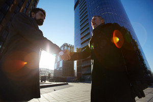 Low angle view of mature entrepreneur in long black coat shaking hand of his business partner as sign of reaching agreement, lens flare