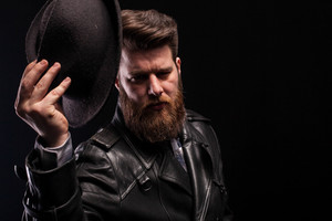 Low key portrait of handsome man holding stylish hat over black background. Bearded man. Dramatic portrait.