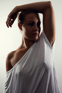 Low-key studio portrait of gorgeous woman with blonde hair and white t-shirt