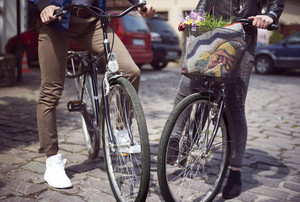 Low section of couple standing with bicycles on street