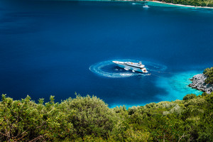 Luxury white yacht sail boat anchoring in a tranquil bay in deep blue water water, near picturesque shore of greek islands