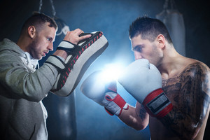 Male boxer sparring with personal trainer