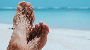 Male Cross Feet at the Sandy Beach, Ocean in Background, Bali