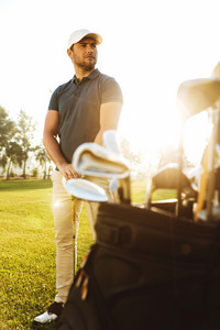 Male golf player at the green sunny course with a club sack