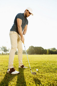 Male golfer about to tee off a golf ball at the green course