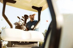 Male golfer in cap standing at the golf cart