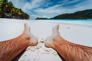 Male legs feet in focus. Enjoying relaxing at tropical paradise beach