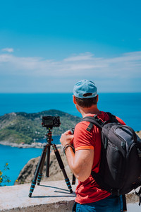 Male photographer with backpack enjoying view to Assos village during capture image from top view point. Camera on tripod