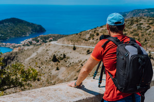 Male summer holiday vacation on Kefalonia Greece. Photographer with backpack enjoying capture of Mediterranean village Assos from top view point. Camera on tripod