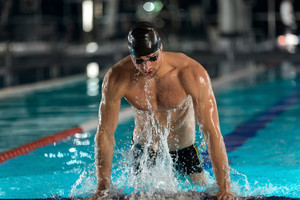 Male swimmer lifting himself out of a swimming pool