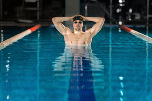 Male swimmer standing in pool with arms on his head