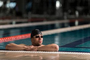 Male swimmer wearing goggles and swimming cap resting on the edge of a swimming pool