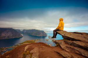 Male tourist sitting on the cliff. Beautiful mountain landscape of Lofoten islands, Reine, Norway.