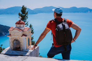 Male tourist staying near small Hellenic shrine Proskinitari admire sea coastline shape landscape. Amazing sea view in the background