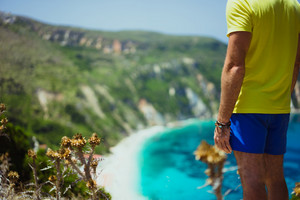 Male tourist wearing shorts on Petani beach Kefalonia enjoying picturesque panorama of emerald azure bay lagoon surrounded by steep cliff coastline. Greece