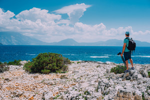 Male tourist with camera admiring breathtaking cloud scenery over the mountain range at the Mediterranean sea coast. Sunning outdoor scene of Ionian Islands, Kefalonia, Greece