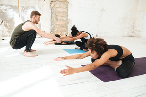Male yoga instructor helping a woman to do yoga stretches in a studio