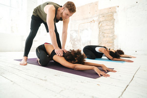 Male yoga instructor helping woman to stretch in a gym