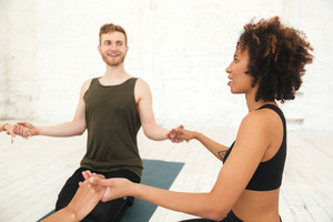 Male yoga instructor sitting in a circle with a group of women and holding hands meditating in a gym