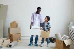 Man and boy holding boxes while making housework together