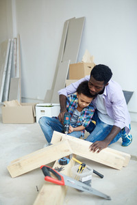 Man and boy using power-tool for drilling wooden plank