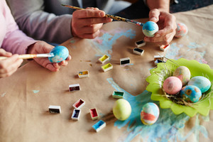 Man and woman painting eggs for religious holiday
