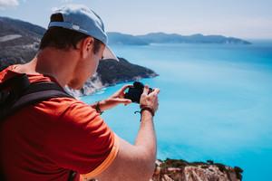 Man capture photograph of myrtos coastline sea landscape. Blue cyan water surface with island shape, Kefalonia, Greece