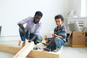 Man drilling wooden plank with his son near by
