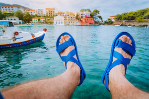 Man feet in sandals over blue water in front of the beautiful assos bay. Kefalonia Greece