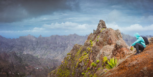 Man hiker with backpack sitting on the mountain top and looking down to the valley. Stunning arid landscape on Santo Antao island, Cabo Verde