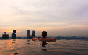 Man In Infinity Pool at Marina Skypark Bay in Singapore Skyline