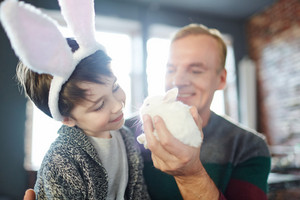 Man showing white fluffy bunny to his son