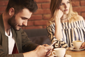 Man using cell phone over meeting with girlfriend