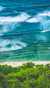 Man walking along of Nunggalan Beach. Big waves rolling on. Uluwatu, Bali, Indonesia