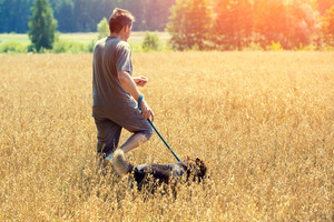 Man with dog on a leash running in an oat field in summer