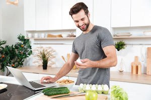 Man with laptop preparing food at the kitchen at home
