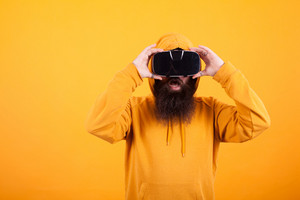 Man with long beard wearing virtual reality headset looking shocked over yellow background. Yellow hoodie. Modern technology. Handsome man.