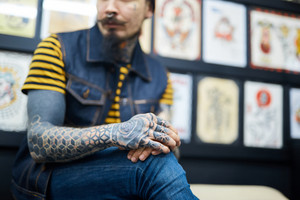 Man with tattooed arms sitting in salon