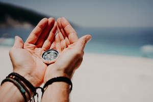 Man's hand holding compass against the backdrop of beach and sea. The concept of travel, summer vacation, holiday and journey