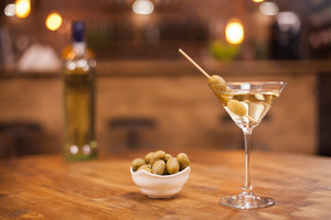 Martini in a glass with olives next to it over a rustic wooden table. Fresh drink. Relaxing drink.