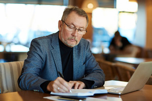 Mature business leader making notes while relaxing in cafe after work