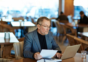 Mature businessman processing or checking data in laptop