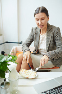 Mature businesswoman having snack at lunch break
